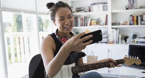 Woman on phone playing the guitar