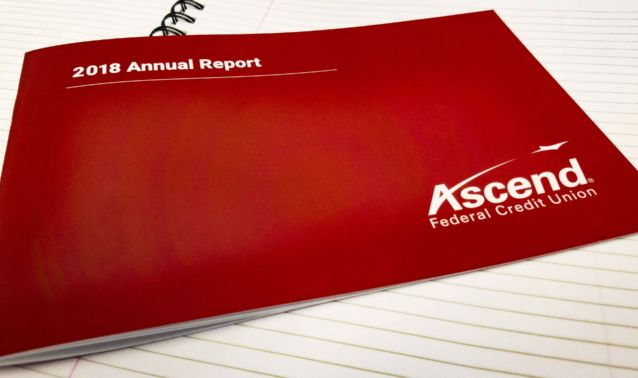 Red annual report booklet on white lined notebook