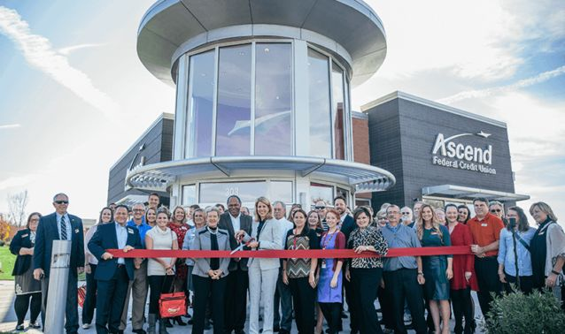 employees in front of ascend office ribbon cutting
