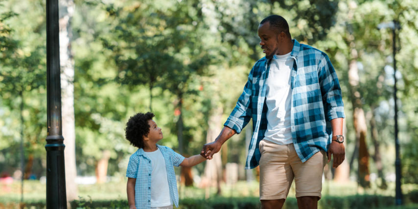 Dad holding sons hand in park