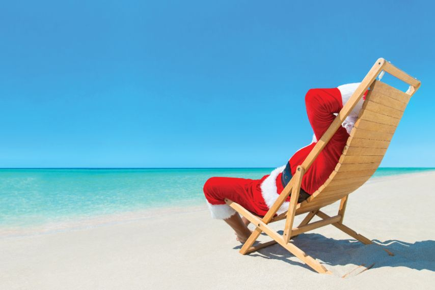 Santa Lounging on Beach with Blue Sky