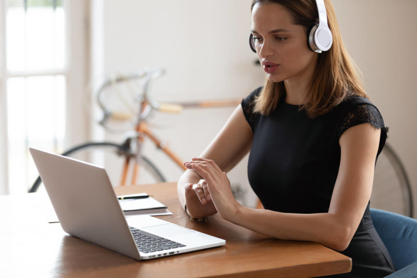 Young woman at laptop wearing headphones