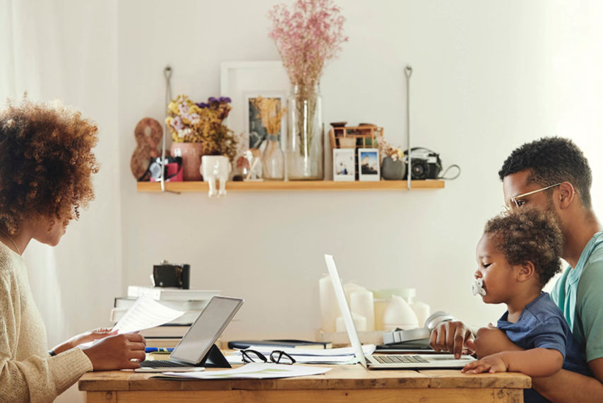 Young African American Family at the table with laptop, tablet, baby