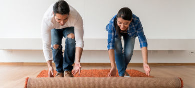 Man and woman roll out carpet
