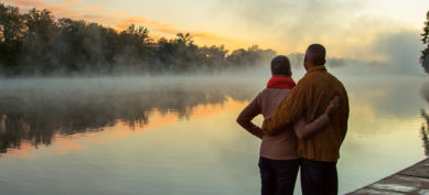 man and woman looking at sunset on the lake