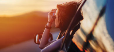Girl looking at sunset in car