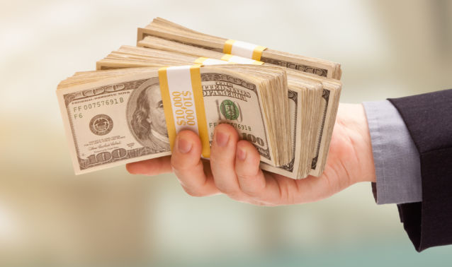 Hand holding stacks of cash