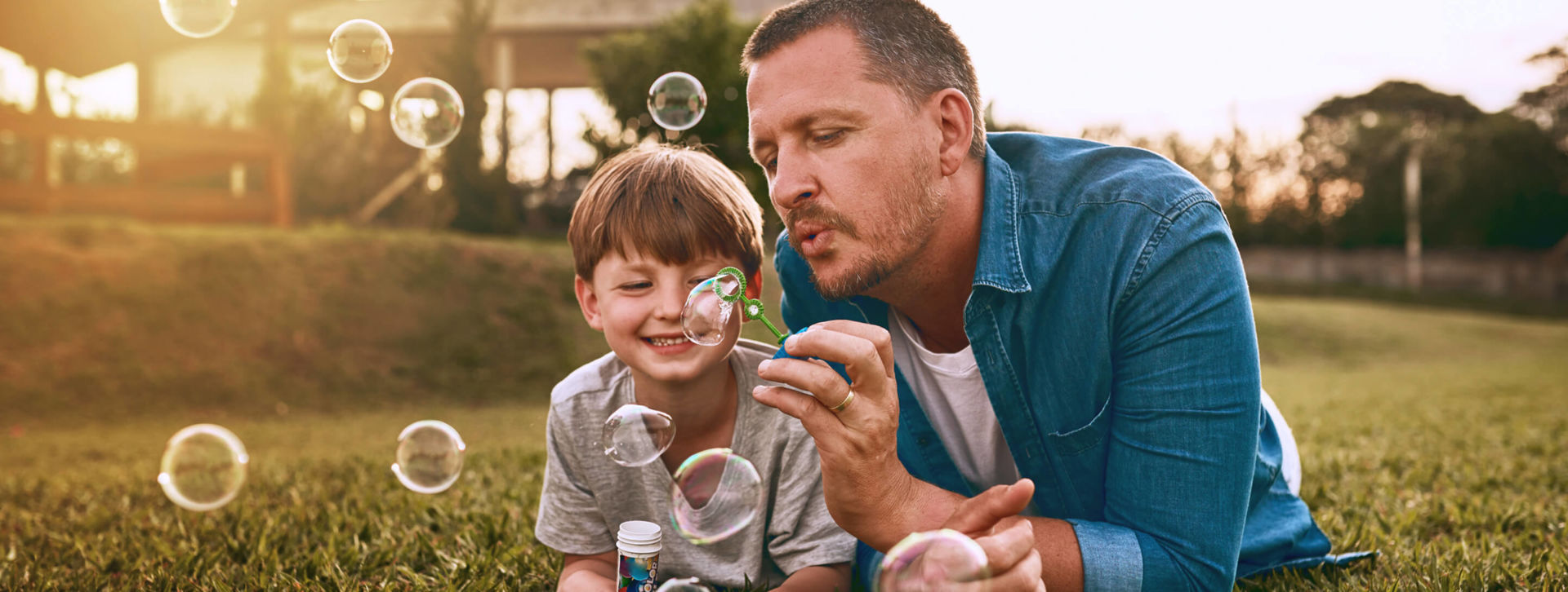 Father and son blowing bubbles in Grass