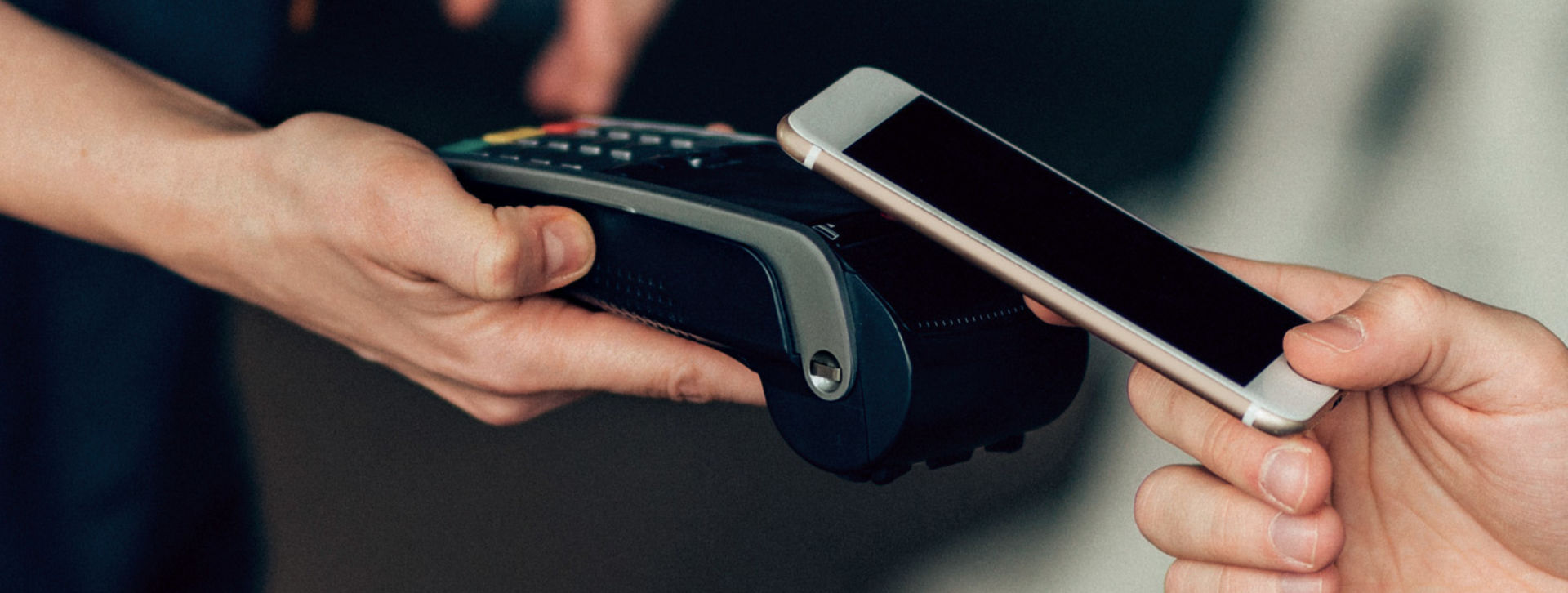hands holding smart phone and credit card processor
