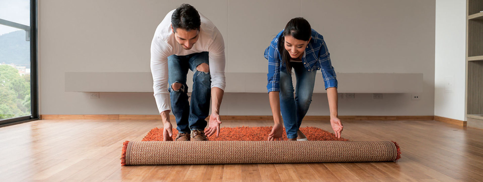 Man and woman rolling out a rug