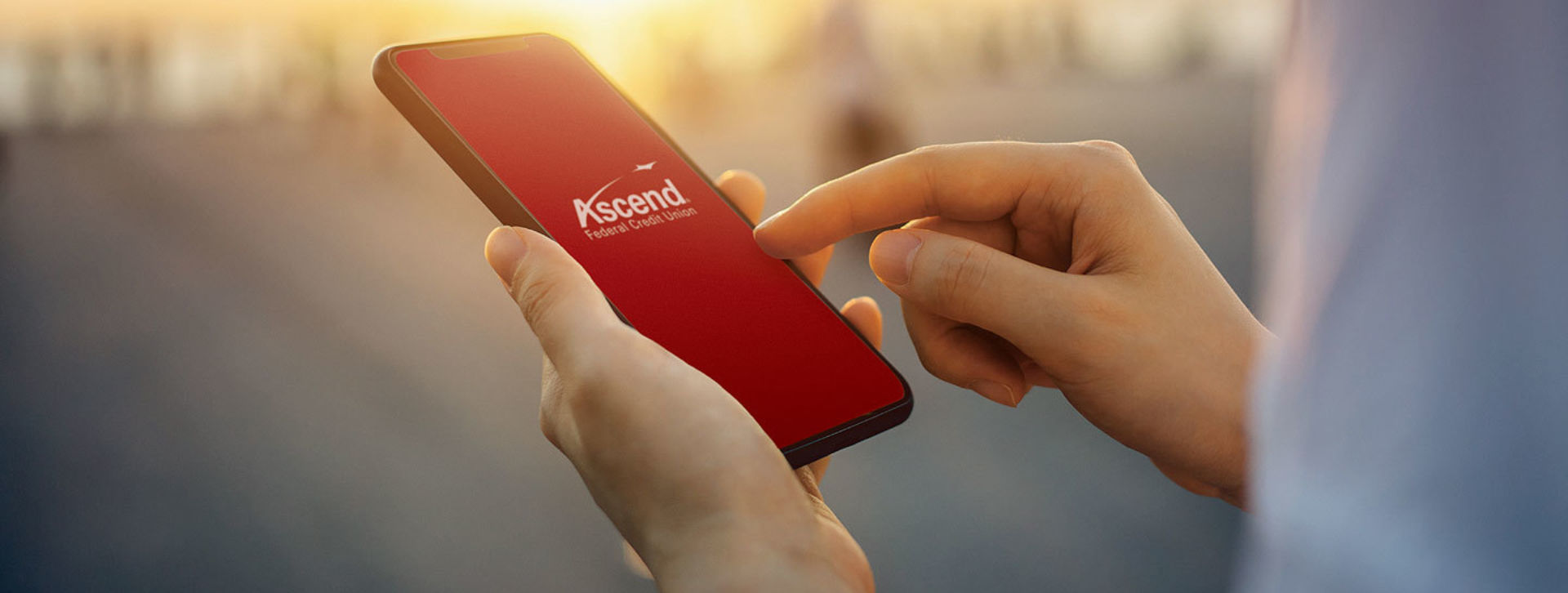 Hands holding a smartphone with Ascend logo