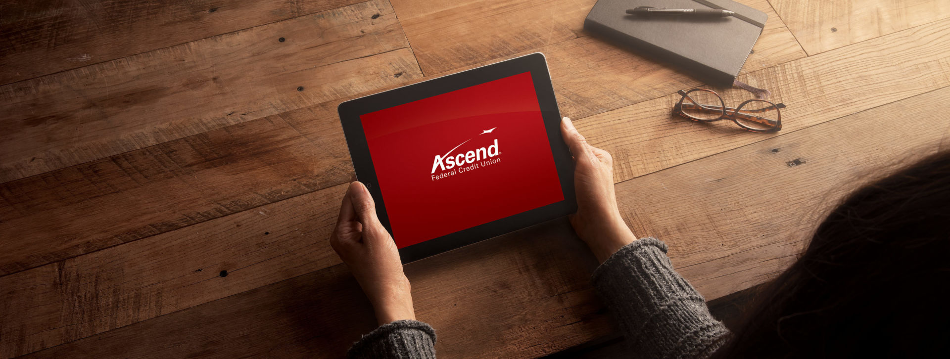 Woman holding tablet with the Ascend logo displayed.