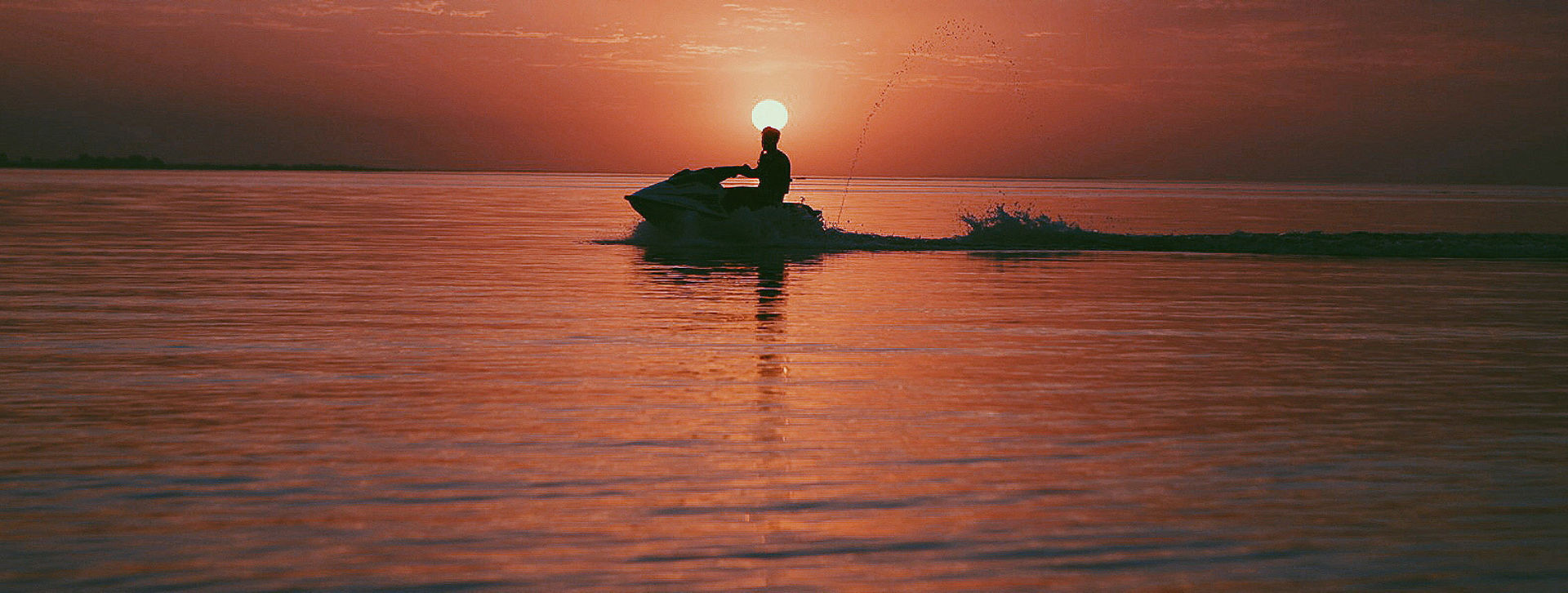 Personal watercraft on water at sunset